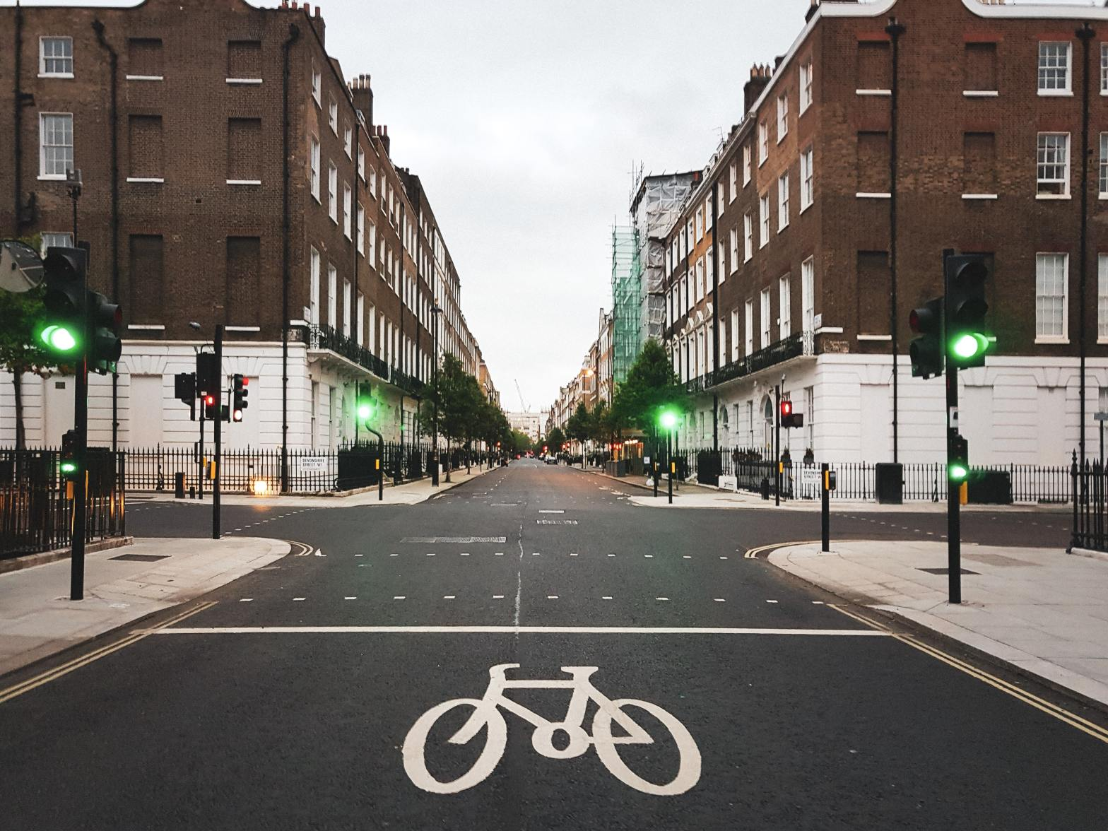 An intersection with a bike symbol painted on the road and brown and white buildings on either side