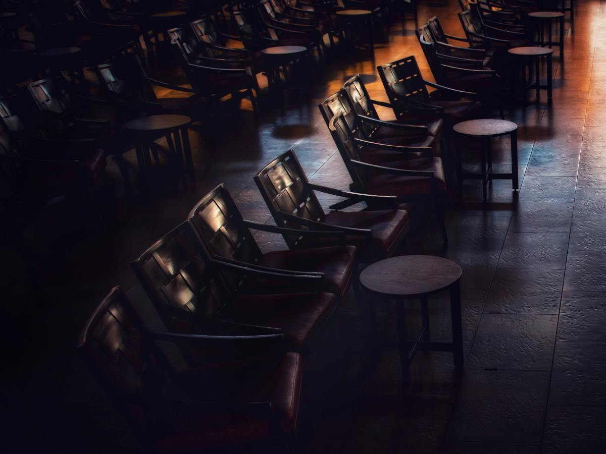 A dark room with chairs and tables in lines